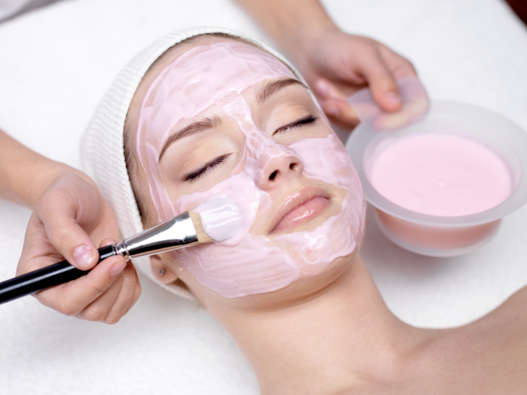 Woman getting pink facial creme mask painted on by skincare specialist.
